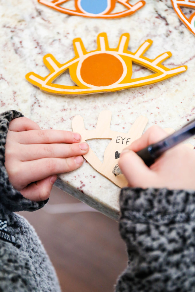 writing a note on the back of a wooden eye-shaped valentine