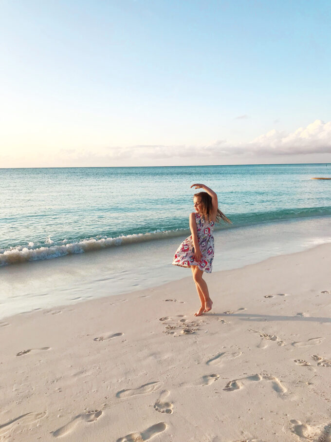 little girl twirling on beach in front of ocean