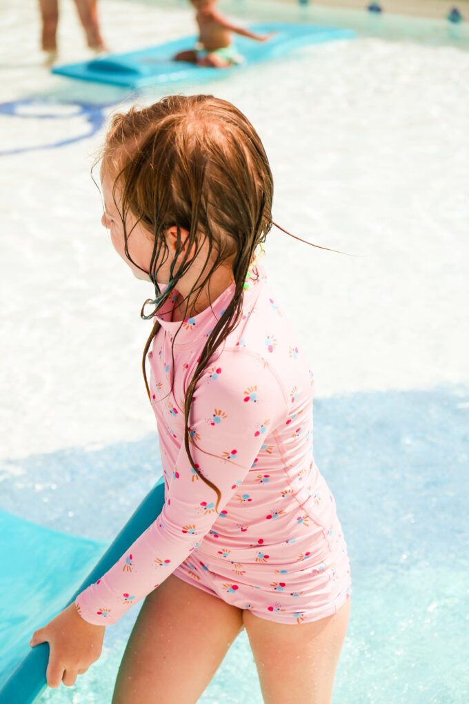 girl holding pool toys
