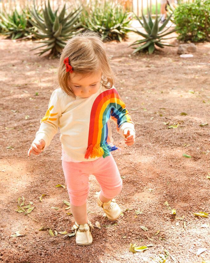 little toddler girl in rainbow sweater