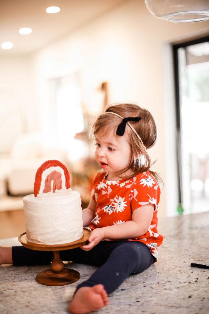 little girl staring at birthday cake
