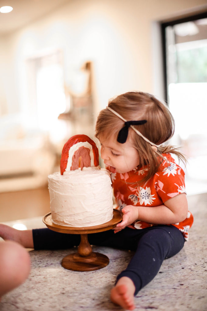 little girl taking a bite out of birthday cake