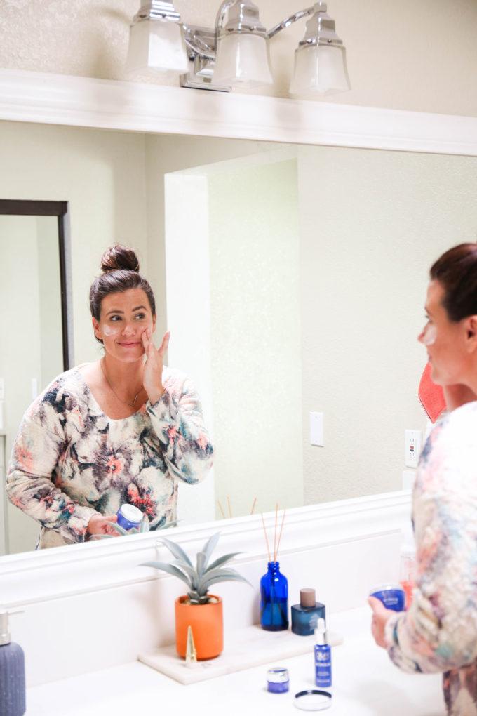 woman applying moisturizer in bathroom mirror