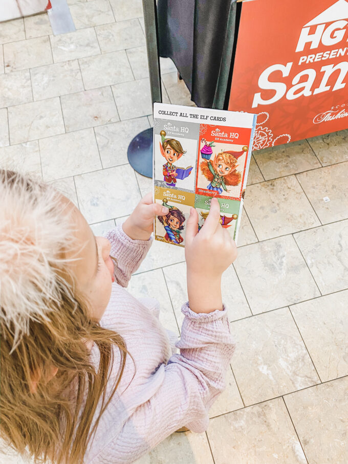 little girl holding elf activity cards