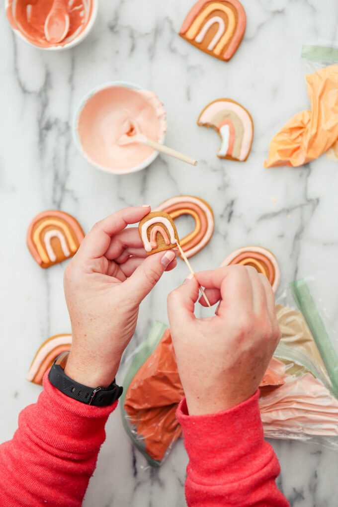 hands holding a cookie and toothpick designing frosting